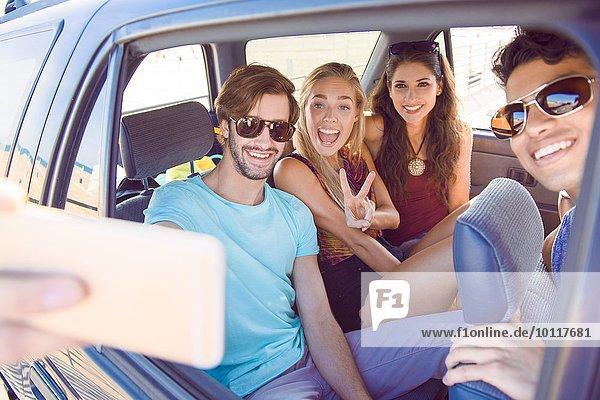 Gruppe von Freunden im Auto sitzend  Selbstporträt mit Smartphone aufnehmend  lachend