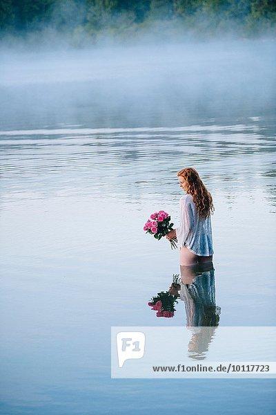 Junge Frau steht im nebligen See und hält Rosenstrauß