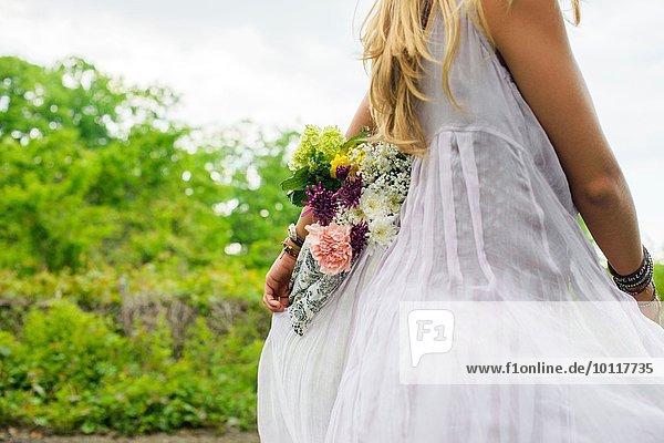 Ausschnitt einer jungen Frau in weißem Kleid mit einem Blumenstrauß auf dem Rücken.