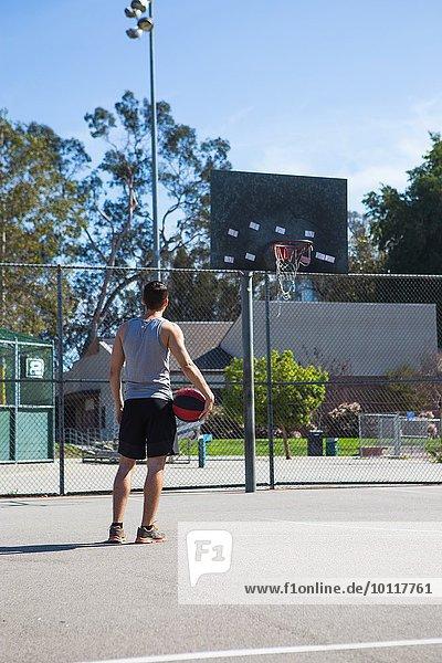 Junger Basketballspieler mit Blick auf Basketballkorb