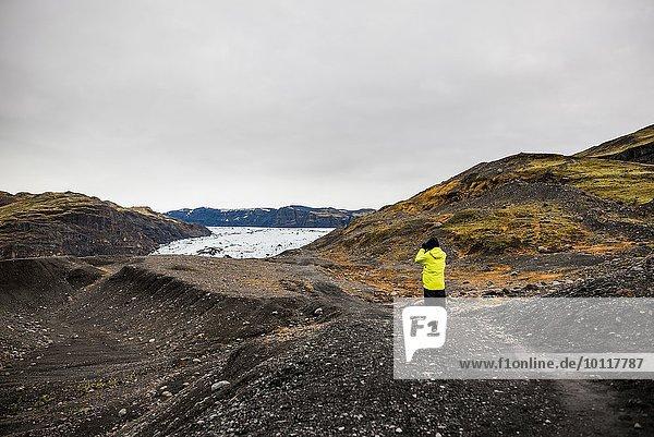 Männliche Touristen fotografieren den Gletscher in Solheimajokull  Island