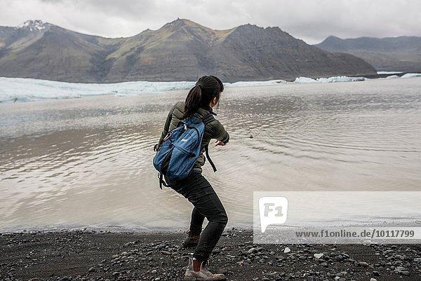 Rückansicht der weiblichen Touristenabschaumsteine im Meer  Skaftafell  Island