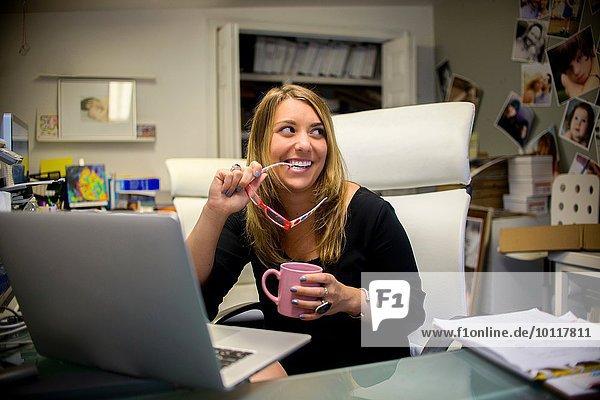 Junge Frau im Büro  sitzt am Schreibtisch  hält Brille und Kaffee.