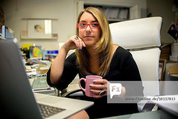 Porträt einer jungen Frau im Büro  am Schreibtisch sitzend  Kaffeetasse haltend