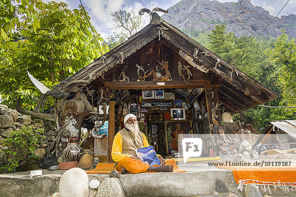 Swami Sundaranand  a famous Sadhu  yogi and photographer  is sitting in front of his house and displaying his book  Gangotri  Uttarakhand  India  Asia
