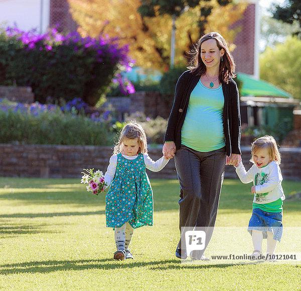 Schwangere Frau läuft mit ihren Töchtern über eine Wiese im Park  Tintenpalast  Windhoek  Namibia  Afrika