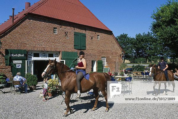 Reiter vor dem Bauernhof-Café auf Gut Görtz  Schleswig-Holstein  Deutschland  Europa