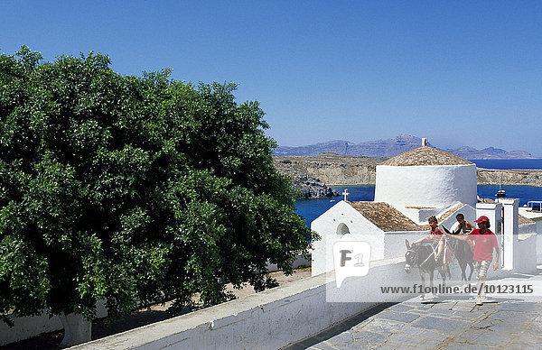 Kinder auf Eseln vor einer Kapelle in Lindos  Rhodos  Dodekanes  Griechenland  Europa