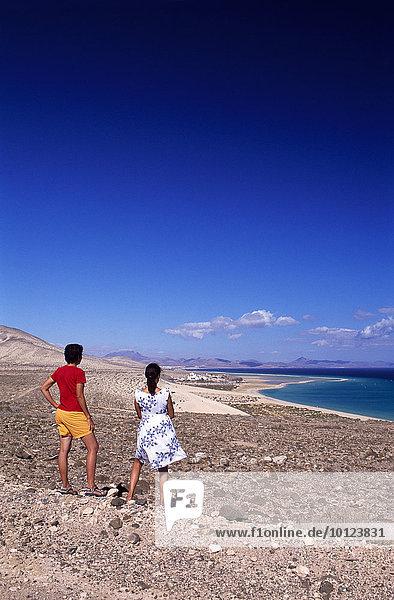 Zwei Menschen  Rückenansicht  mit Blick auf die Küste bei Sotavento  Fuerteventura  Kanarische Inseln  Spanien  Europa