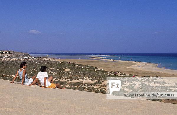 Zwei Menschen sitzen auf Sanddüne bei den Playas de Sotavento  Fuerteventura  Kanarische Inseln  Spanien  Europa