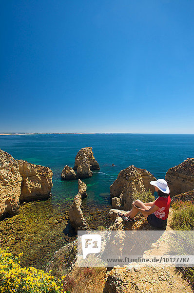 Touristin mit Blick auf die Felsklippen der Ponta da Piedade  Algarve  Portugal  Europa