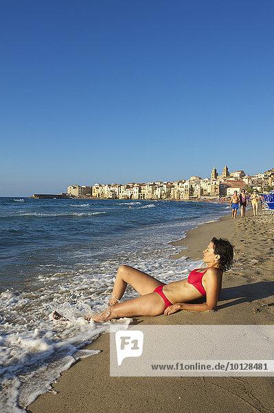 Frau in Bikini liegt am Strand  dahinter die Altstadt  Cefalù  Provinz Palermo  Sizilien  Italien  Europa