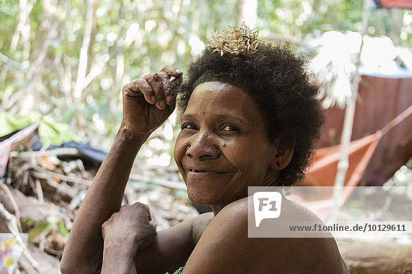 Woman of the Orang Asil tribe sitting in the jungle  portrait  Native  Indigenous Volk  tropical rain forest  Taman Negara National Park  Malaysia  Asia