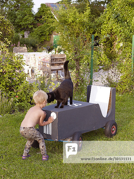 Girl playing in garden with cat
