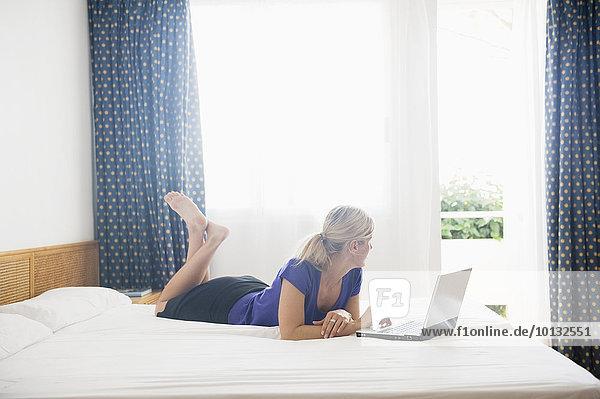 benutzen Frau Notebook Bett