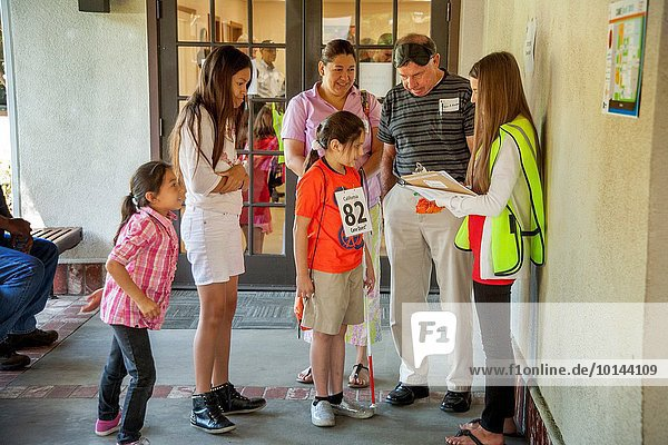 A sighted volunteer helps a blind Hispanic teen and her family during Cane Quest,  a program to teach self reliance to young blind people and their families in Anaheim,  CA. Note white cane and young sister at left.