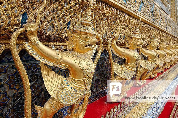 Garuda and Nagas  at the outside of the ubosot of Wat Phra Kaew - Temple of the Emerald Buddha; full official name Wat Phra Si Rattana Satsadaram  the historic centre within the precincts of the Grand Palace  Phra Nakhon District  Bangkok  Thailand.