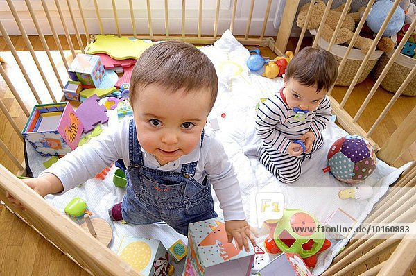 Junge - Person Zwilling - Person 12 Baby Monat alt spielen Laufstall
