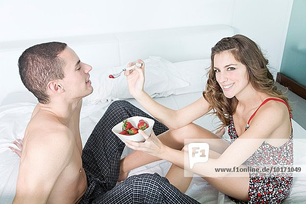 Young couple in bed eating strawberries