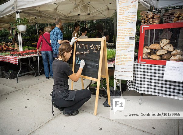 A workers at a farmers´ market in New York posts their egg prices