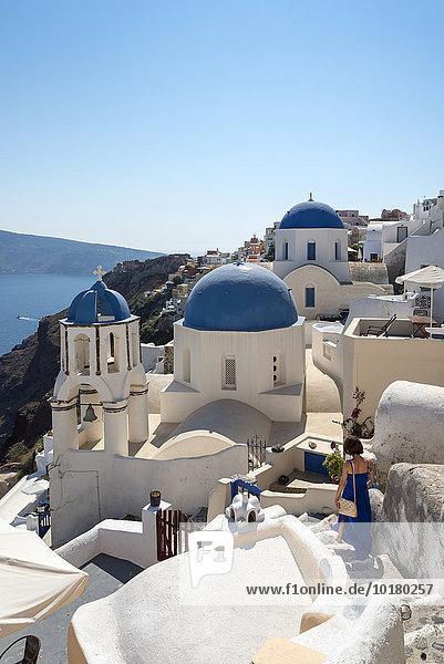 Frau geht zu Fuß durch die blauen Kuppeln der Kirche von Agios Spiridonas und die Kirche von Anastasis  Oia  Santorin  Griechenland  Europa