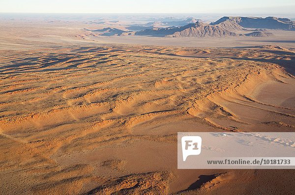 Luftbild aus einem Heißluftballon  Bauernhaus am Fuße einer großen grasbewachsenen Düne am Rande der Namib-Wüste  NamibRand-Naturreservat  Namibia  Afrika