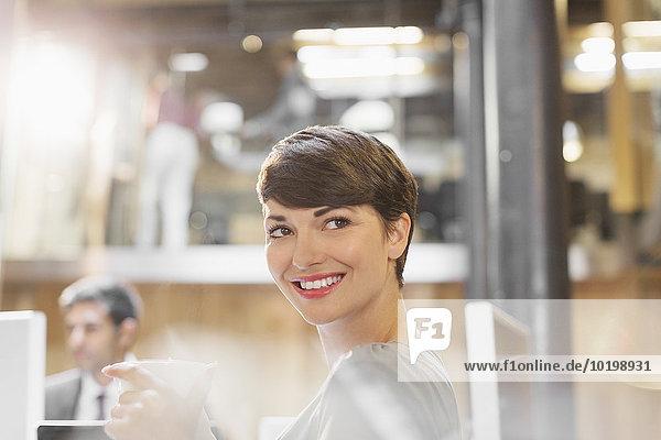 Lächelnde Geschäftsfrau beim Kaffeetrinken im Büro