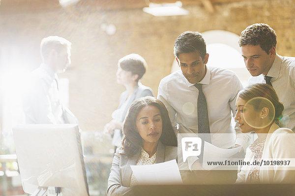 Geschäftsleute  die den Papierkram im Büro prüfen