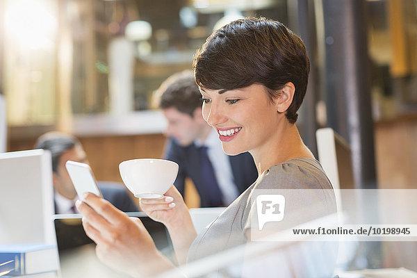 Geschäftsfrau trinkt Kaffee und SMS mit Handy im Büro