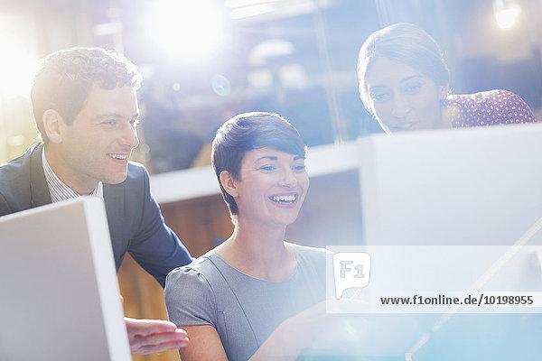 Lächelnde Geschäftsleute am Computer im Büro