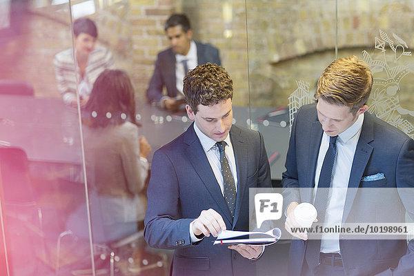 Geschäftsleute diskutieren Papierkram außerhalb der Konferenzraumbesprechung