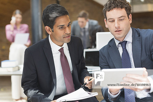 Geschäftsleute  die im Büro mit digitalen Tabletts arbeiten