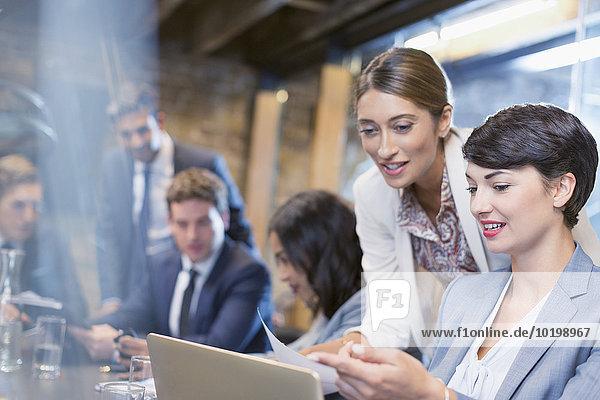 Geschäftsfrauen bei der Arbeit mit digitalen Tabletts in Konferenzräumen