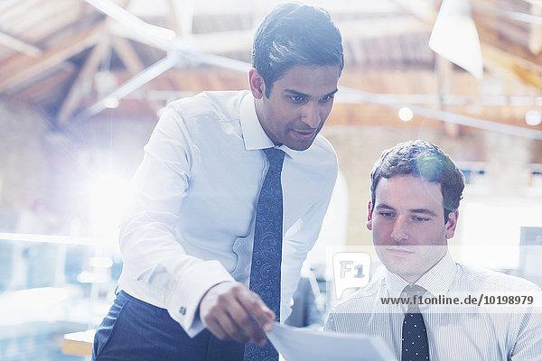 Geschäftsleute beim Lesen von Papierkram im Büro