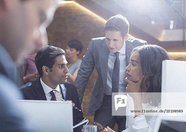 Ernsthafte Geschäftsleute reden im Büro