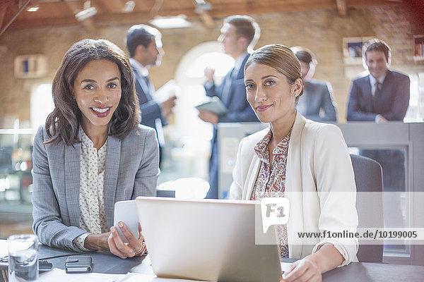 Portrait selbstbewusste Geschäftsfrauen bei der Arbeit am Laptop im Büro