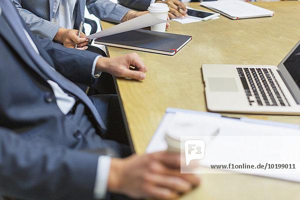 Geschäftsmann trinkt Kaffee am Laptop in der Sitzung