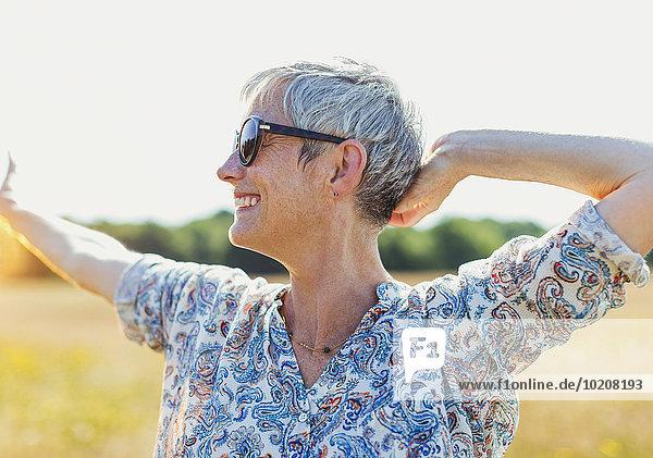 Enthusiastische Seniorin mit ausgestreckten Armen im sonnigen Feld