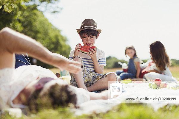 Lächelnder Junge isst Wassermelone auf Decke im sonnigen Feld