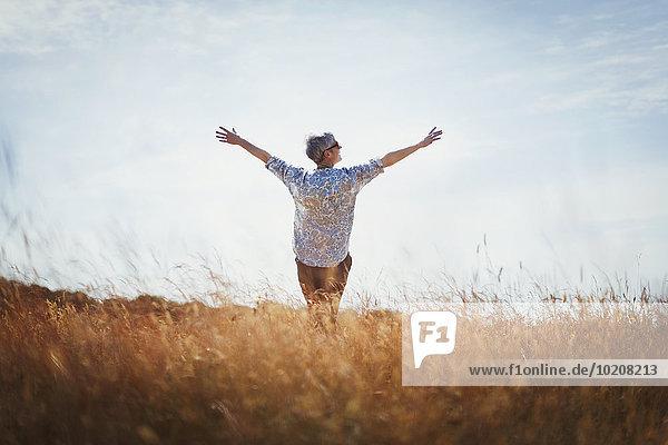 Überschwängliche Seniorin mit ausgestreckten Armen im sonnigen Feld