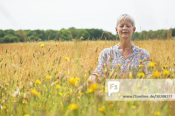 Seniorin beim Meditieren im ländlichen Raum