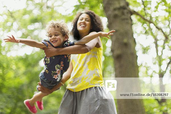 Verspielte Mutter fliegt Sohn unter Baum