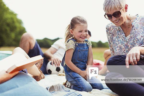 Großmutter und Enkelin lachend auf Decke