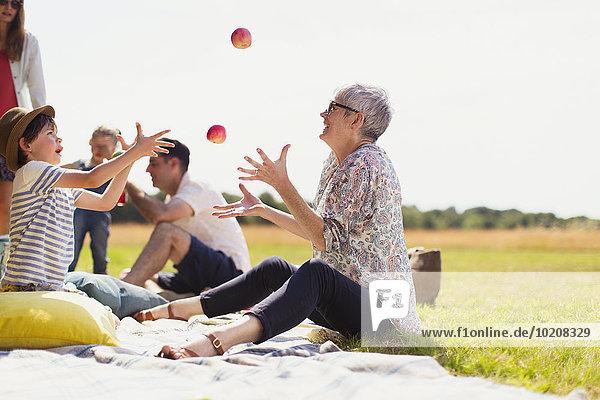 Großmutter und Enkel jonglierende Äpfel auf Picknickdecke im sonnigen Feld