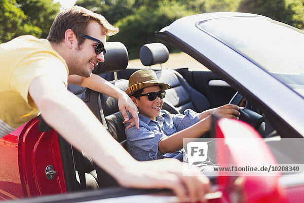 Vater beobachtet Sohn  der vorgibt  im Cabrio zu fahren.