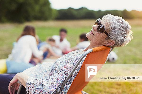 Seniorin entspannt sich im Stuhl im Feld