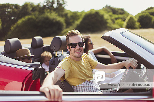 Portrait lächelnder Mann im Cabriolet mit Familie