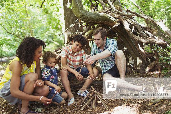 Familie macht kleines Lagerfeuer im Wald mit Stöcken