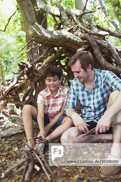Vater und Sohn machen ein kleines Lagerfeuer mit Stöcken im Wald.