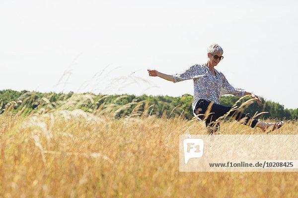 Verspielte Seniorin tanzt im sonnigen ländlichen Raum